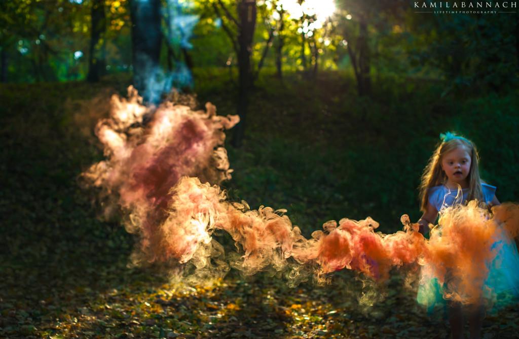 Dziewczynka z Zespołem Downa wśród kolorowego dymu. Sesja stylizowana na Alicję w Krainie Czarów.