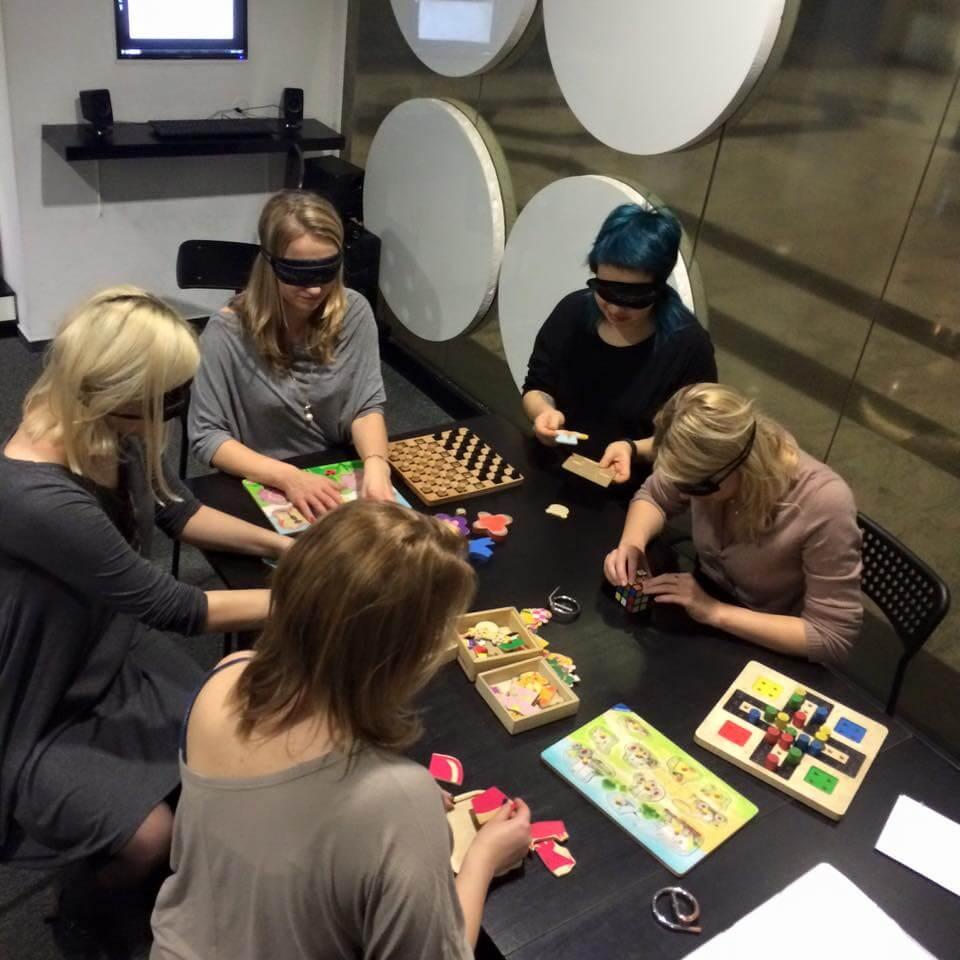 Geek Girls Carrots na Niewidzialnej Wystawie układają puzzle z zasłoniętymi oczami.