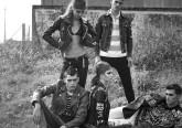 5 osób w punkowych strojach na polanie.