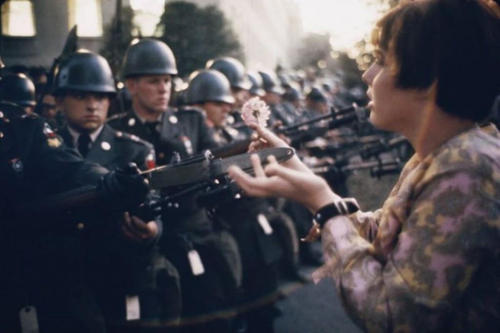 fot. Marca Riboud, Jane Rose Kasmir zakłada kwiat na bagnet żołnierza pilnującego Pentagonu w czasie protestów przeciwko wojnie w Wietnamie, 21 października 1967r.